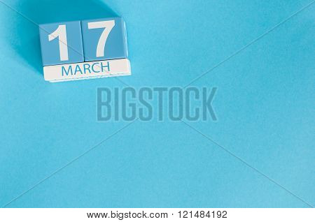 Happy St Patricks Day save the date. March 17th. Image of march 17 wooden color calendar on blue bac