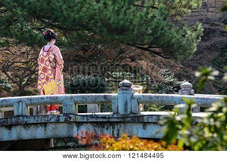 Young geisha woman on a bridge in Maruyama Park, Kyoto during spring