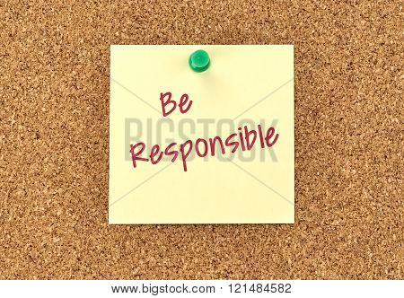 The phrase Be Responsible in red text on a yellow sticky note posted to a cork notice board.