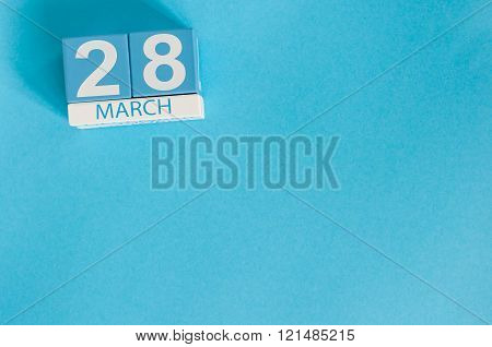 March 28th. Image of march 28 wooden color calendar on blue background.  Spring day, empty space for