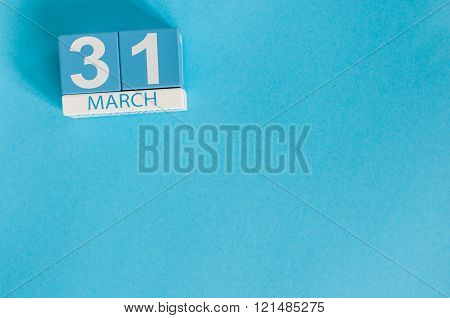 March 31st. Image of march 31 wooden color calendar on blue background.  Spring day, empty space for