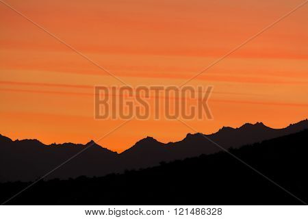 Dramatic sunset in the hills of Palm Springs shows beautiful striations in a deep orange sky