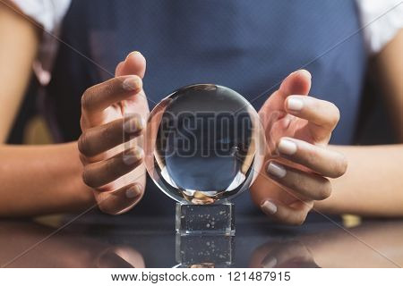 Businesswoman using crystal ball on black background