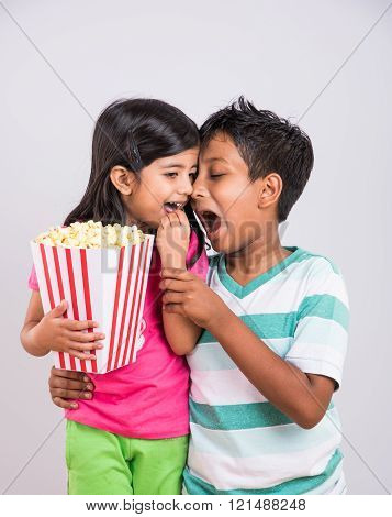 asian little boy and girl watching movie with pop corn