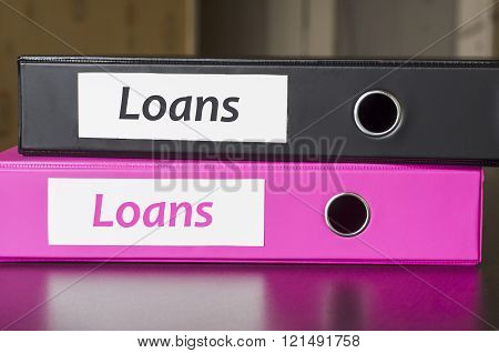 Bright office folders over dark background and loans text concept