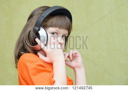 Beautiful Girl With Headphones On Her Head Attentively Listens To Music