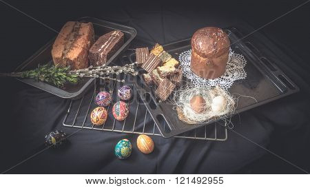 Easter Still Life with traditional holiday elements. Eggs pysanka bread cake willow tree brunches. Dark food styling