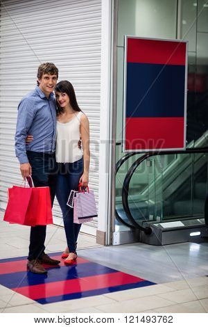 Couple with shopping bag standing near escalator in shopping mall