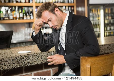 Tired man having a whiskey in a pub