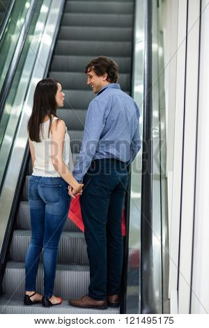 Couple standing and holding hand on escalator in mall