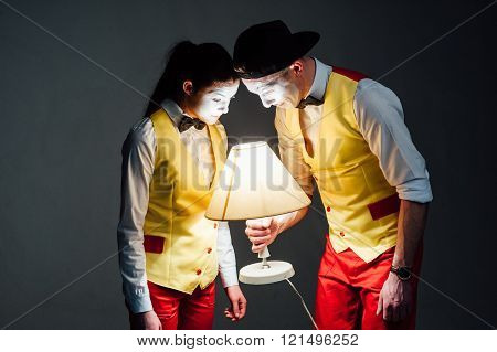 studio shot of two mimes isolated on a gray background. muffled light. look at the lamp