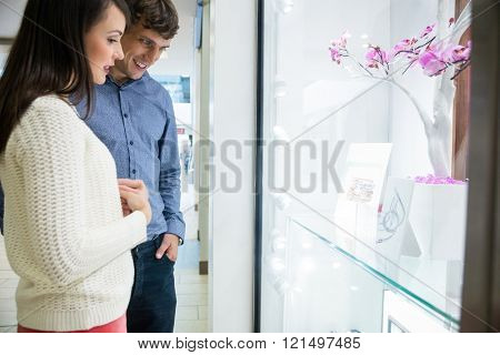 Couple looking at window display in shopping mall