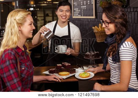 Smiling friends enjoying pastries at the coffee shop