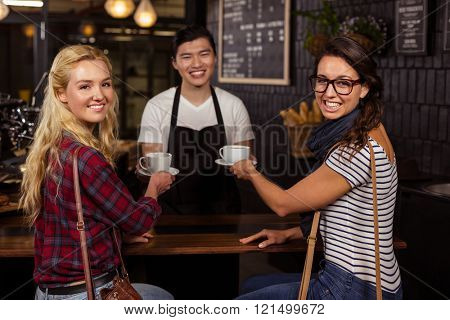 Smiling waiter serving a coffee to customers at the coffee shop