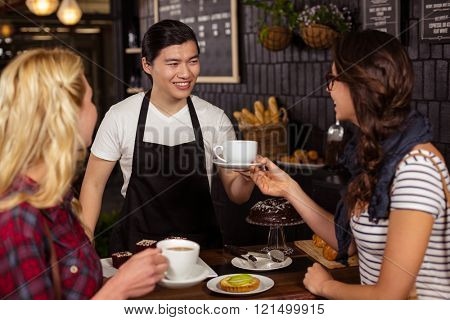 Smiling waiter serving a coffee to a customer at the coffee shop