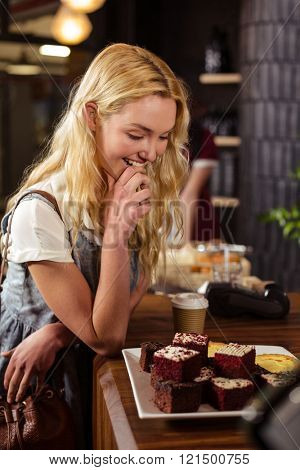 Pretty customer admiring cakes at coffee shop