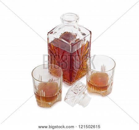 Decanter and two glasses with whiskey on a light background