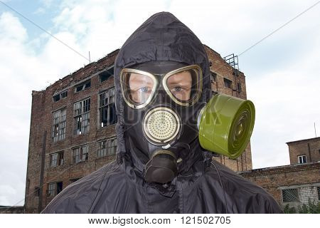 Person In Gas Mask Against The Backdrop Of Abandoned Building