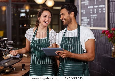 Smiling baristas using tablet in the bar