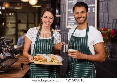Smiling baristas holding sandwiches and hot milk in the bar