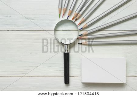 magnifying glass, pencils and blank business card on wooden table. Copy space for text