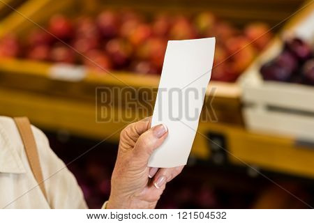 Female consumer holding a receipt in supermarket