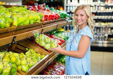 Smiling woman holding plastic bag with apples in supermarket