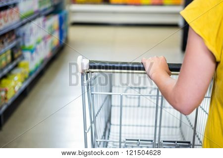 Detail of woman pushing cart in supermarket