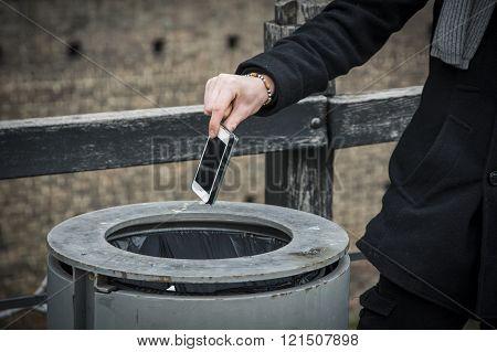 Man throwing phone in garbage bin