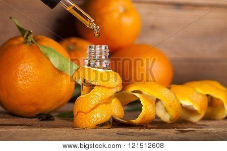 Bottle of essential oil from oranges on wooden background - alternative medicine