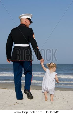 Marine And Daughter Walking At The Beach