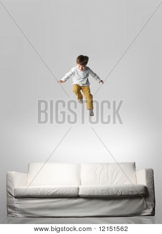 child jumping on a sofa