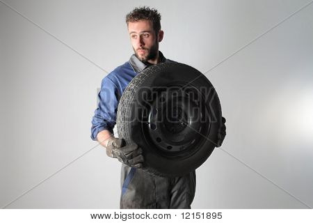 Portrait of auto mechanic holding a  wheel  isolated on a white background