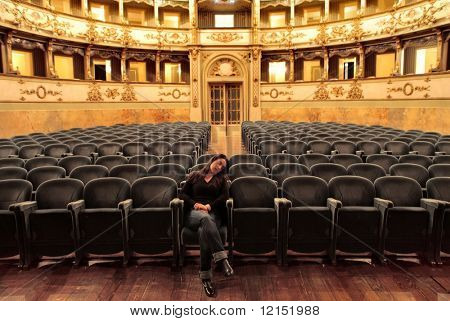 woman falling asleep in empty theater