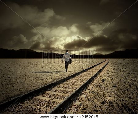 man walking along train tracks