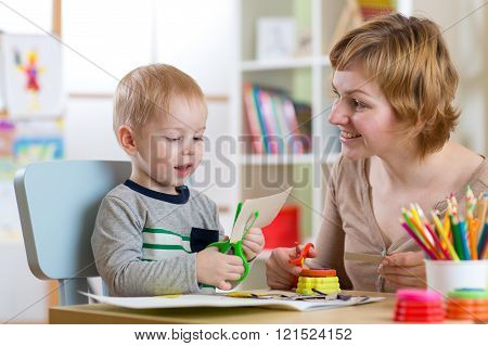 Woman teaches child handcraft