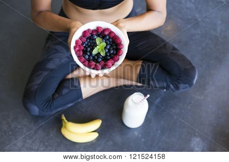 Above shot of a woman with a bowl of berries, a bottle of almond milk and two bananas wearing a sportive outfit. non-diary
