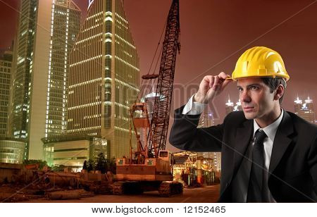 a business man in hard hat against an erection yard