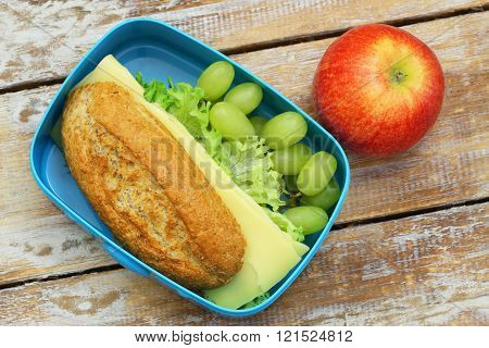 Healthy lunch box containing whole grain bread roll with cheese and lettuce, grapes and apple