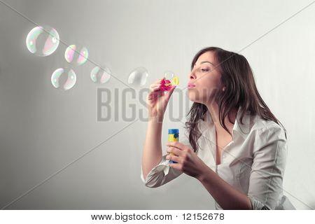 Linda chica haciendo pompas de jabón