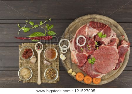 Spices and raw beef shank on the cutting board. Preparing spicy food. Decorations for the menu