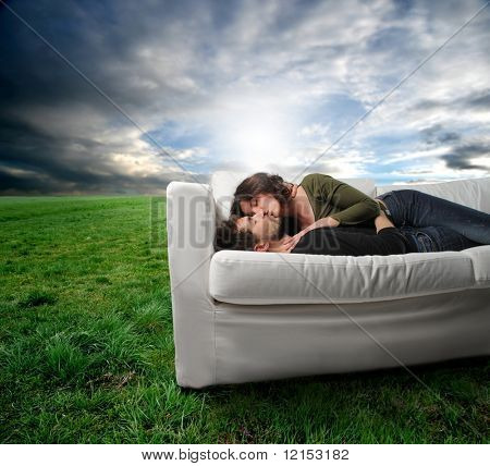 young couple in effusion on a sofa in a grass field