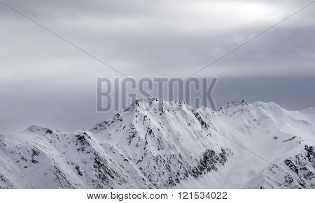 High Snowy Mountains And Gray Sky Before Blizzard
