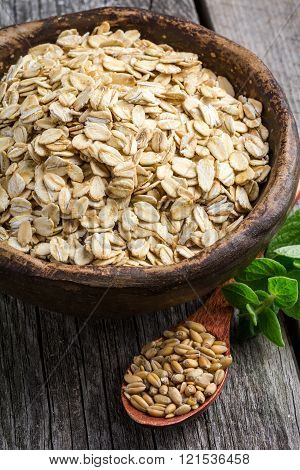 Rolled oats and oat grains in bowl on wooden background