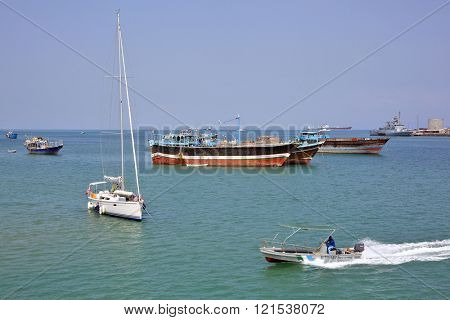 GULF OF ADEN, DJIBOUTI â?? FEBRUARY 08, 2016: Coast Guard boat goes by luxury sailing boat, fishing and cargo ships at anchor in the port of Djibouti