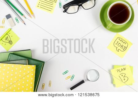 Office table desk with green supplies, blank note pad, cup, pen, glasses, crumpled paper, magnifying