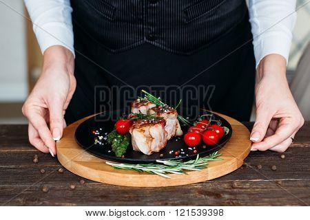 Food  serving. Chief serving a pork dish.