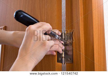 hands with screwdriver screwing hinge on a door