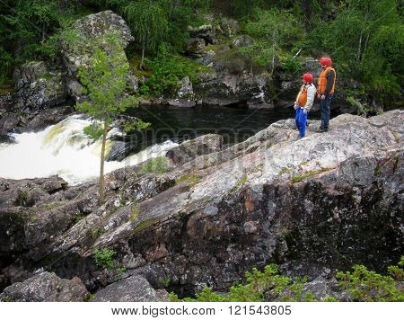 KOLA PENINSULA RUSSIA - AUGUST 11 - Men in the life vest examines threshold mountain river in Kola Peninsula on August 11 2008.