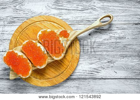 Sandwiches with red caviar on wooden cutting board, on a plank table with copy space.